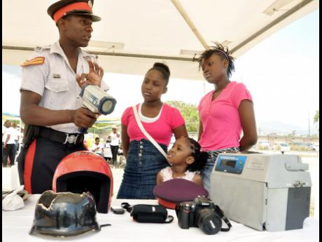 Police Corporal Daniel Bennett (left) of the Traffic Division explains why it is neccesary to use a speed gun to Shanique Weathers (centre), Juanielle James (right), and Jada James during the Road Wise Expo 2015 under the theme 'Be Road Wise & Save Lives', held on Saturday at the Police Officers' Club in St Andrew